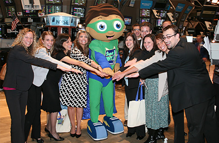 Grand Communications' Alison Grand and Jaymie Presberg with Super Why, star of the PBS KIDS series, along with Out the Blue co-founders, show creators and executive producers, Samantha Freeman and Angela C. Santomero, bring some literary-powered fun to the trading floor of The New York Stock Exchange after ringing The Closing Bell